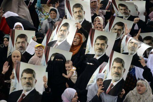 Female Egyptian supporters of the Muslim Brotherhood hold up portraits of Egypt's ousted president Mohamed Morsi during a rally in Cairo on July 21, 2013. (AFP Photo)