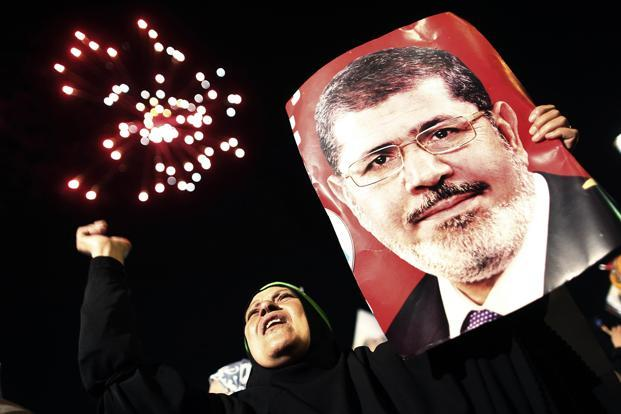 A woman holds a portrait of ousted Egyptian President Mohamed Morsi as thousands of Muslim Brotherhood members and supporters of Morsi rally at Raba Al Adaawyia mosque on 4 July in Cairo.  (AFP Photo)