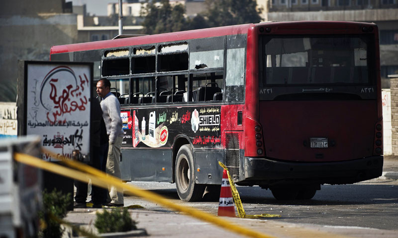 Egyptian security officials inspect the wreckage of a bus that was damaged by an explosion on 26 December 2013 in Cairo.  (Photo by AFP)
