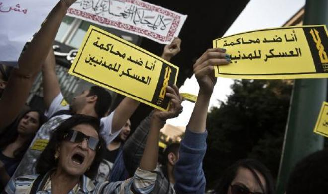 """Egyptian protesters hold placards shouting slogans during a demonstration organized by the group """"No Military Trials for Civilians"""" in front of the Shura council in downtown Cairo on November 26, 2013 (AFP File Photo)"""