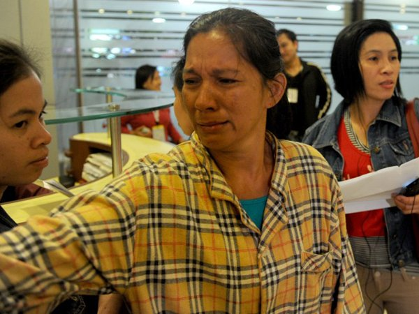 Filipina domestic helper Amor Roxas (C), 46, weeps upon arriving at the Philippines' main international airport on Nov 4, 2013 as she recounts her ordeal after being expelled from Saudi Arabia, where an amnesty for illegal workers expired at the weekend. (AFP Photo)