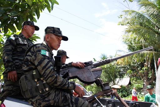 File photo taken on February 11, 2013 shows MILF rebels standing guard near the venue where Philippine President Benigno Aquino will be attending a ceremony as part of his visit to the rebels' stronghold in Sultan Kudarat on Mindanao island  (AFP/File, Richele Umel)