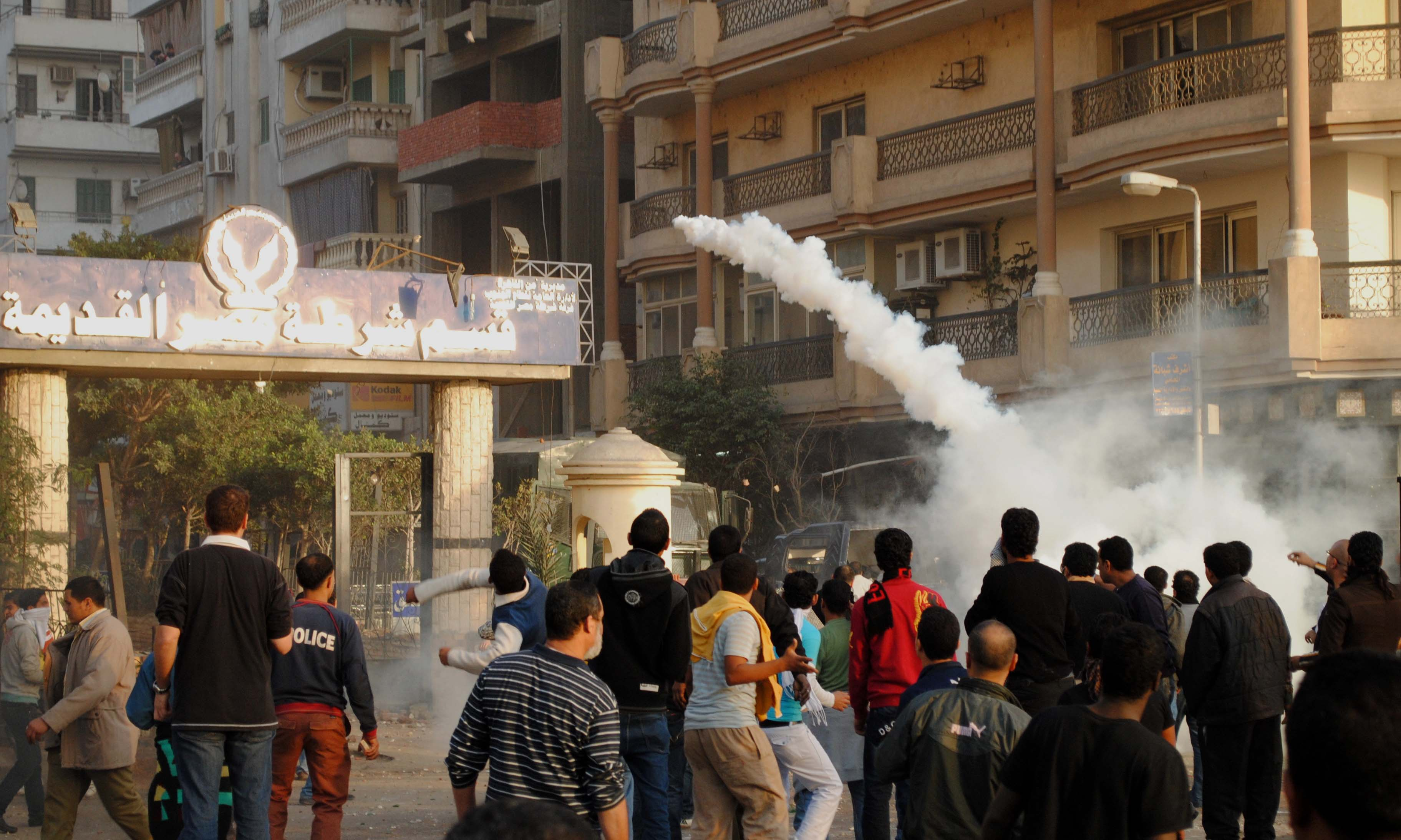 Protesters throw a tear gas canister back at police forces outside a police station on the Friday of Anger, 28 January 2011