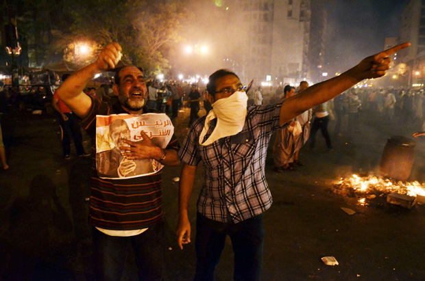Supporters of deposed president Mohammed Morsi hold a picture of him during a rally in Cairo's Ramsis square under the Six of October bridge on July 15, 2013. (AFP Photo)