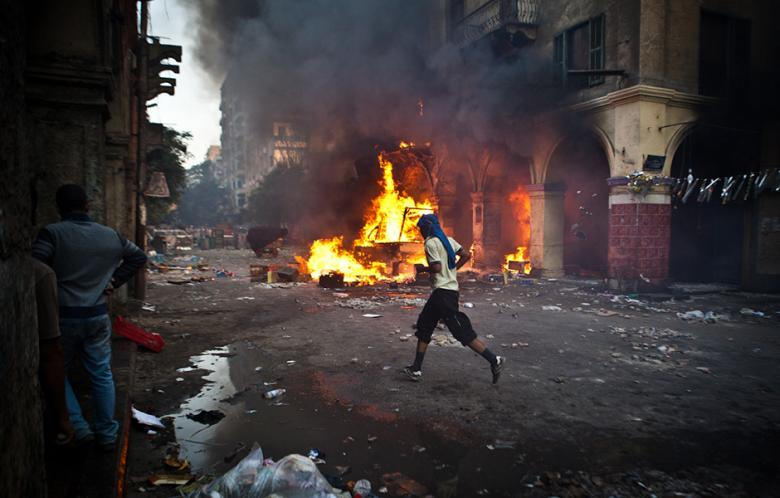 A supporter of the Muslim Brotherhood and of ousted president Mohamed Morsi runs past a burning vehicle during clashes with security officers close to Cairo's Ramses Square, on 16 August 2013.  ( AFP Photo / Virgnie Nguyen Hoang)