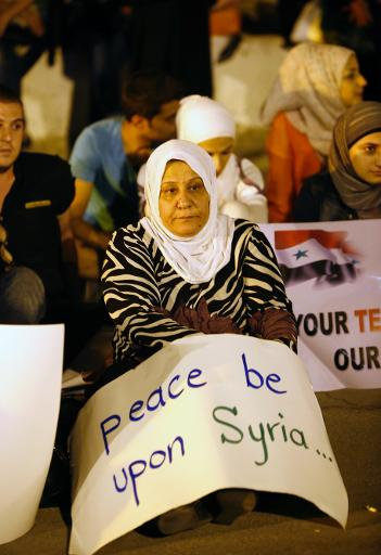 A woman holds a placard for peace during a sit-in protest against a military action on Syria on September 13, 2013 in Damascus (AFP/File, Anwar Amro)