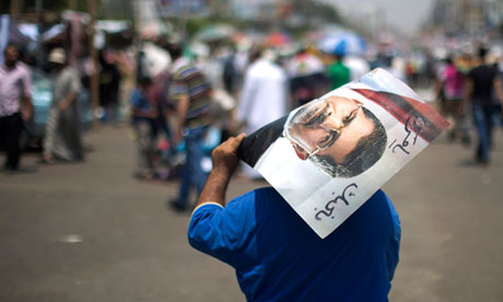 An Egyptian supporter of the Muslim Brotherhood walks holding a poster of Egypt's deposed president, Mohamed Morsi.  (Mahmud Hams/AFP)
