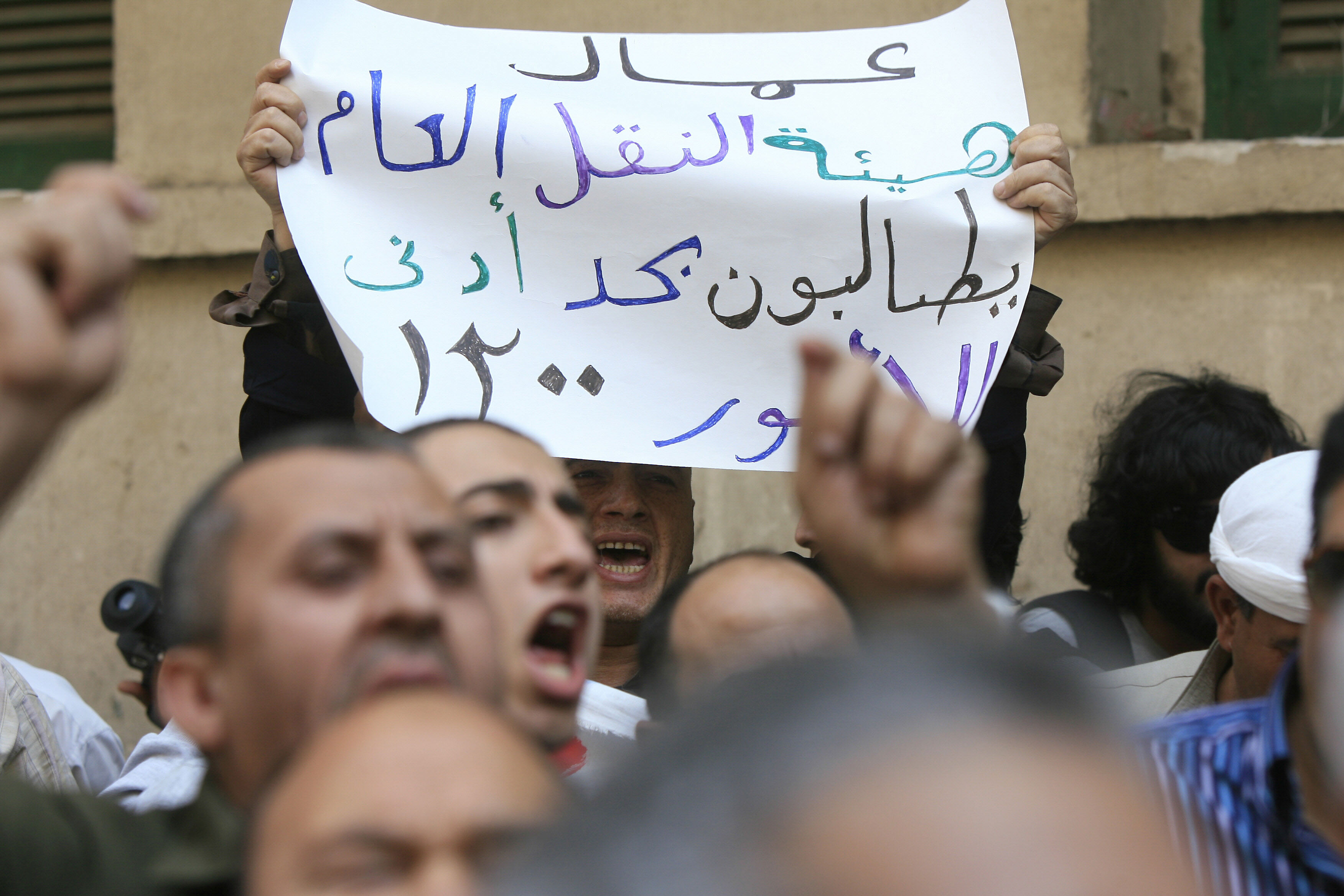 An Egyptian man holds a sign calling for a higher minimum wage during a protest outside the parliament building in downtown Cairo on May 2, 2010.  Several demonstrations were staged in years leading to the 2011 revolution in demand of a monthly minimum wage of 1,200 pounds. The government's decision, although aimed to placate workers, was met with decry as living expenses soared, and a maximum ceiling for public officials was not set.  (AFP FILE PHOTO/KHALED DESOUKI)