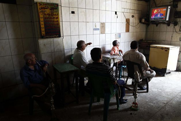 Egyptians sitting in a traditional coffee shop watch TV in Cairo in 2012 (AFP File Photo)