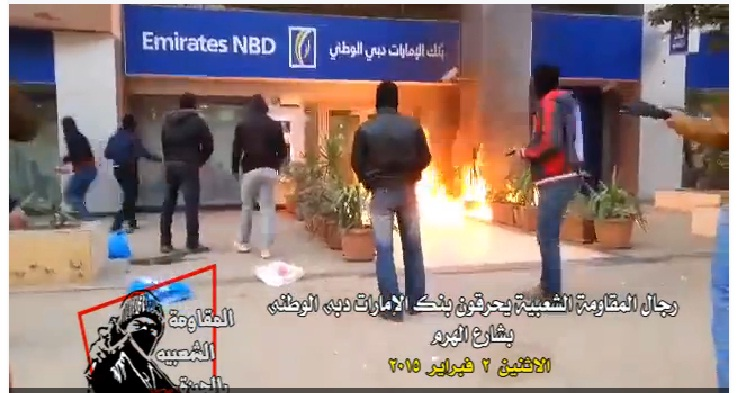 Militant group 'Popular Resistance in Giza' released a two-minute video showing masked gunmen setting fire to an Emirates National Bank branch in Haram Street in Giza. (Photo Screenshot from Popular Resistance in Giza)