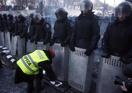 A demonstrator places signs in front of riot police as Ukrainian journalists protest against police violence in Kiev on January 27, 2014  (AFP, Yuriy Kirnichny)
