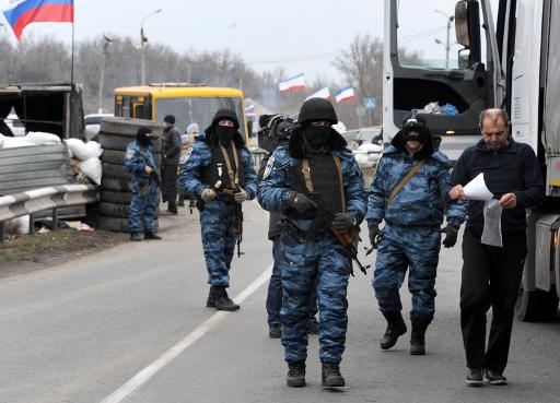 Armed masked men who call themselves members of Ukraine's disbanded elite Berkut riot police force man a checkpoint under a Russian flag on a highway near the city of Armyansk, on February 28, 2014  (AFP, Viktor Drachev)