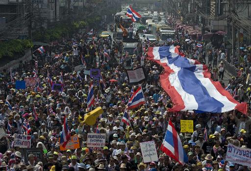 Thai anti-government protesters carry a large national flag as they parade during a rally in Bangkok on January 25, 2014  (AFP/File, Pornchai Kittiwongsakul)