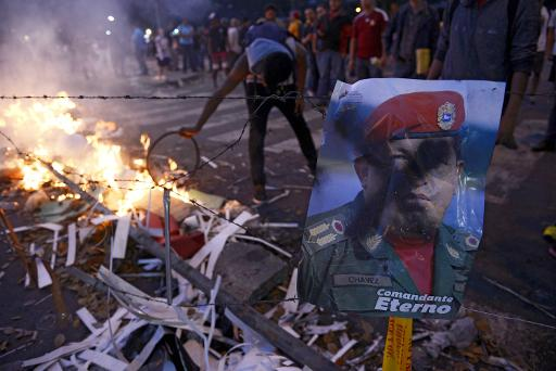A protester lights a barricade next to a poster of late Venezuelan president Hugo Chavez during an anti-government demonstration in Caracas on February 21, 2014 (AFP, Leo Ramirez)