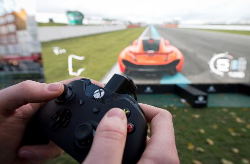 "A man plays the ""Forza 5"" driving game on a massive screen at a launch party for the new Microsoft Xbox One console in central London on November 21, 2013 (AFP, Leon Neal)"