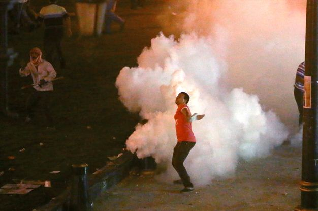A supporter of Mohamed Morsi throws back a tear-gas canister shot by riot police in Cairo, July 16, 2013 (AFP, Marwan Naamani)