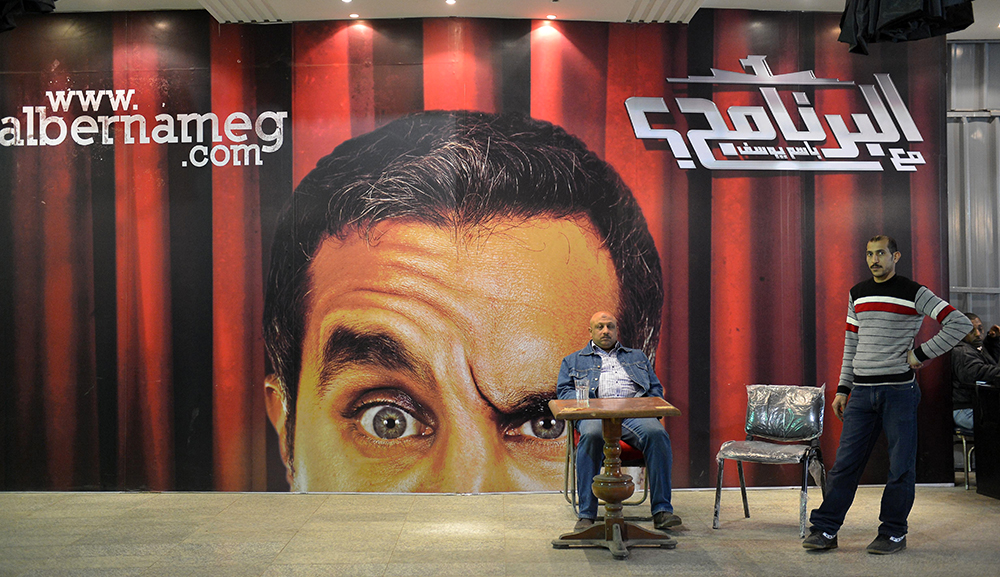 Egyptians gather in front of a poster of Egyptian satirist Bassem Youssef at a theater in Cairo. (KHALED DESOUKI/AFP/Getty Images)