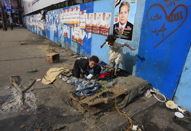 Homeless Egyptian children play near electoral campaign posters in Giza, southwest of Cairo on Dec. 13 ahead of the second phase of voting in parliamentary elections. (Mohammed Abed/AFP/Getty Images)