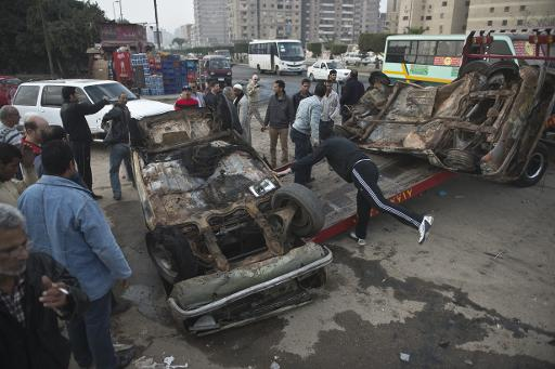 Local men remove damaged cars that were set on fire by Muslim Brotherhood supporters, during clashes with police in Nasr city district in Cairo, on January 8, 2014  (AFP/File, Khaled Desouki)