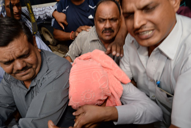 Indian policemen escort the juvenile (C, in pink hood), accused in the December 2012 gang-rape of a student, to a court in New Delhi on August 31, 2013.  (AFP Photo)