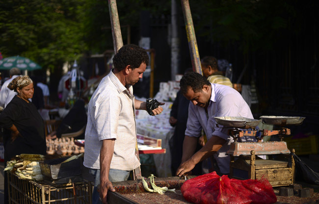 An Egyptian man buys food from a street vendor at an open air market in Cairo. [Gianluigi Guercia/AFP]
