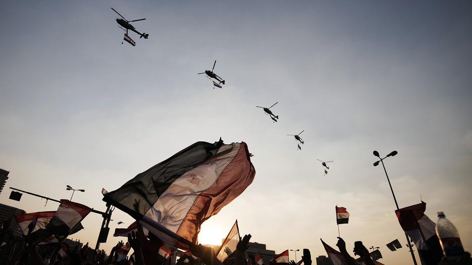 Egyptians wave their national flag as army helicopters fly over Cairo's Tahrir Square on July 4, the day after the military ousted President Mohammed Morsi. (AFP File Photo)