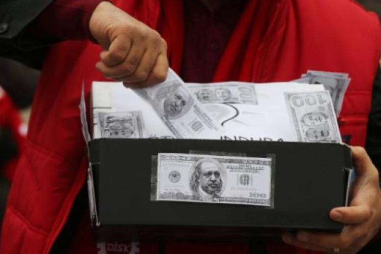 A demonstrator carries a shoe box, a symbol of the corruption scandal after police found $4.5 million secreted in shoe boxes in the home of the chief executive of Turkish state-owned Halkbank. (AFP Photo)