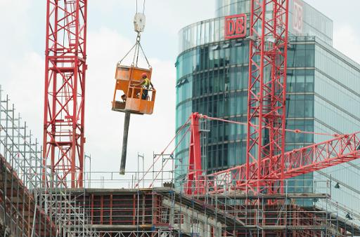 A worker is lifted by a crane on a construction site for a new shopping mall in Berlin on August 1, 2013  (AFP/File, John Macdougall)