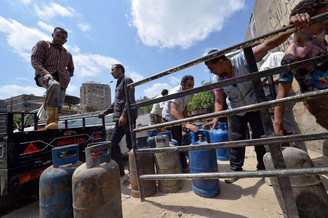An Egyptian man loads gas cylinder onto a truck to be refilled at a warehouse in Cairo  (AFP PHOTO / KHALED DESOUKI)