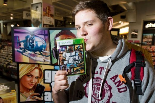 "Taylor Pelling poses with his copy of ""Grand Theft Auto V"" at the HMV music store in central London, September 17, 2013  (AFP/File, Leon Neal)"