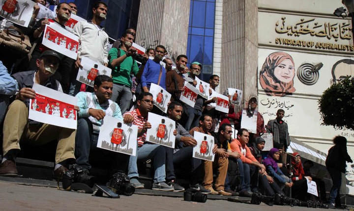 Journalists and photojournalists hold banners as they demonstrate in front of the journalist's syndicate in Cairo against repeated attacks on members of the press in Egypt on April 4, 2014. (AFP PHOTO / MAHMOUD KHALED)