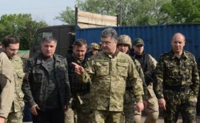 Ukrainian President Petro Poroshenko (center), wearing military fatigues, speaks with Ukrainian army's Anti-Terrorist Operation officers near the eastern Ukrainian city of Izyum, during his visit of the Donetsk region, on June 20, 2014.  (AFP / SERGEY BOBOK)