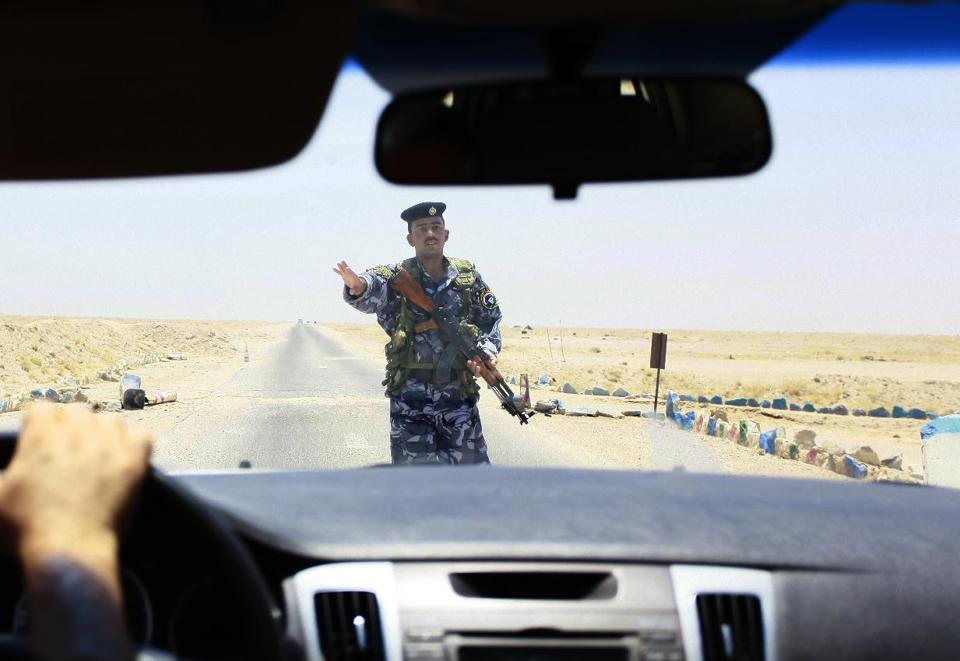Iraqi Shiite fighters secure an area west of the central holy city of Najaf on a road leading to the restive Anbar province, on June 28, 2014  (AFP Photo/Haidar Hamdani)