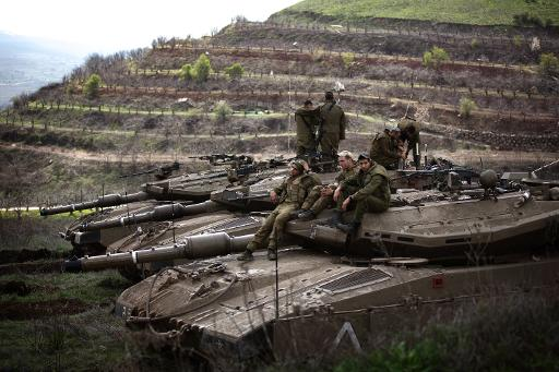 Israeli soldiers sit on their Merkava tanks after being deployed on the border with Syria near the Druze village of Majdal Shams, on March 19, 2014  (AFP, Menahem Kahana)