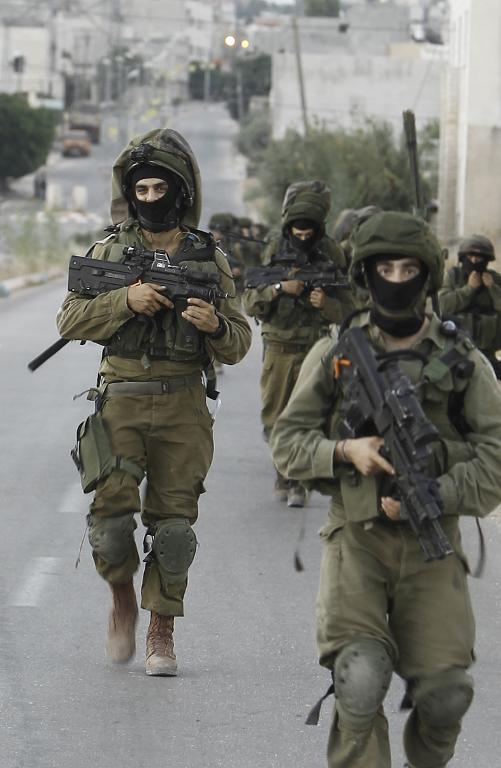 Israeli soldiers patrol a street in the West Bank village of Beit Furik, southeast of Nablus, early on June 20, 2014, as they take part in a search for three teenagers believed kidnapped by Hamas