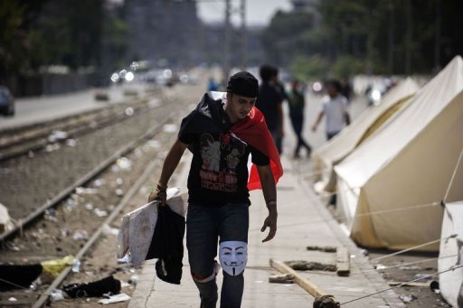 An Egyptian protester walks past opposition supporter tents outside the presidential palace in Cairo on July 1, 2013 (AFP, Gianluigi Guercia)