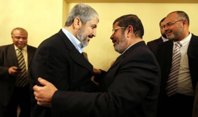 A handout provided by the Hamas press office shows Khaled Meshaal (left) embracing Mohamed Morsi during a meeting in Cairo  (AFP File Photo)