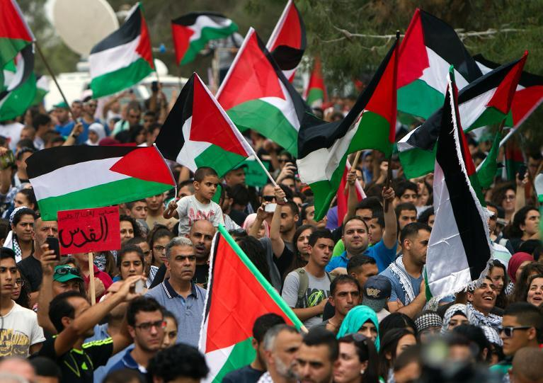 Arab Israelis protesters hold up the Palestinian flag as they march for the right of return for Palestinian refugees who fled their homes or were expelled during the 1948 war, during a protest rally near Tiberias in northern Israel, on May 6, 2014  (AFP Photo/Ahmad Gharabli)