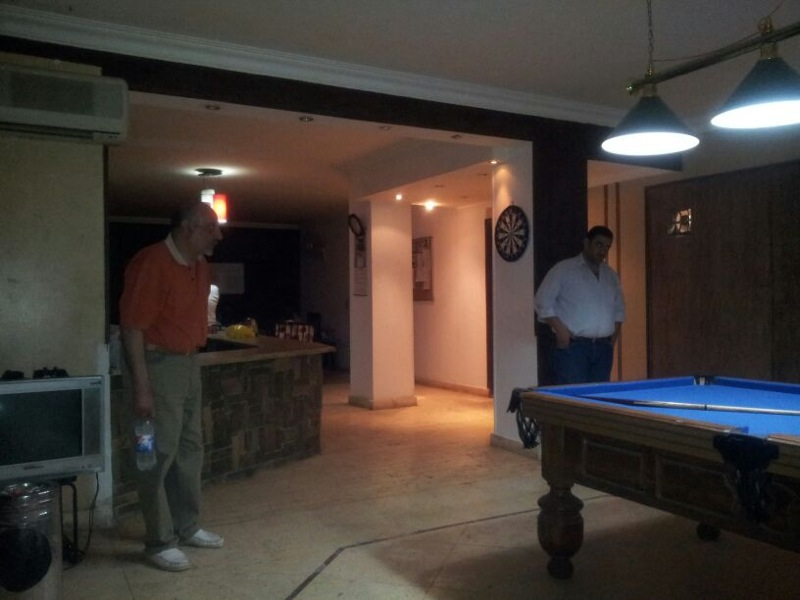 Dr Ahmed Dawoud and Am Atef at billiard table watching rehab centre residents playing a game (Photo By Ethar Shalaby)