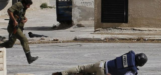 Reporter Sammy Ketz, hits the ground as a Syrian soldier runs past during sniper fire in the Christian Syrian town of Maalula, ins September, 2013 (AFP Photo)
