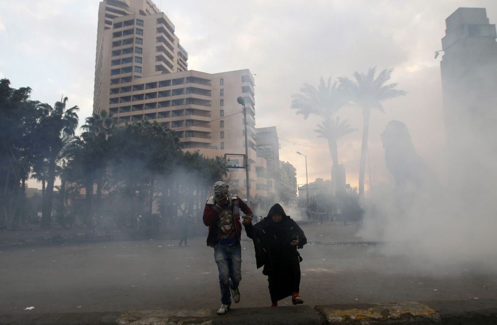 An Egyptian protester helps a woman take cover from tear gas during clashes with riot police near Cairo's Tahrir Square on January 29, 2013.  (AFP File Photo)