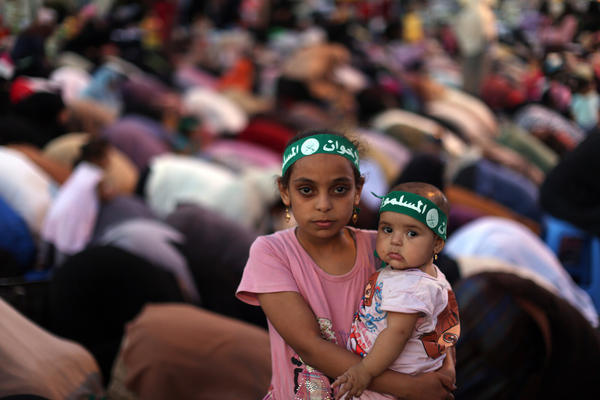 An Egyptian girl holds a baby as Egyptian supporters of the Muslim Brotherhood and Egypt's ousted president Mohamed Morsi pray outside Cairo's Rabaa al-Adawiya mosque.  ( MAHMUD HAMS / AFP/Getty Images / July 10, 2013 )