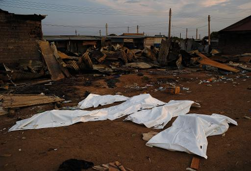 Dead bodies covered in plastic lie in front of a burnt out marketplace in Bor on February 1, 2014  (AFP, Carl De Souza)