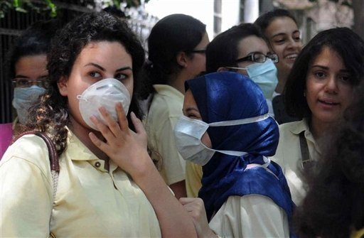 Egyptian high school students girls wear protective masks as they leave school in Cairo (AFP File Photo)