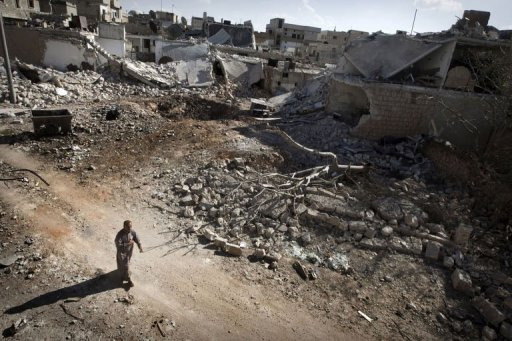 A man walks through a destroyed residential area of the Syrian city of Saraqib (AFP/File, Giovanni Diffidenti)