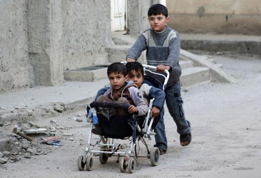 A boy carries two younger boys in a pushchair on February 8, 2014 in a street of the northeastern Syrian city of Deir Ezzor (AFP, Ahmad Aboud)