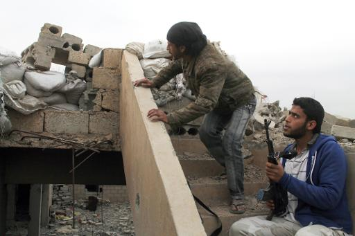 Rebel fighters look over a makeshift barricade constructed on the roof of a building in the northeastern Syrian city of Deir Ezzor, on March 24, 2014  (AFP, Ahmad Aboud)