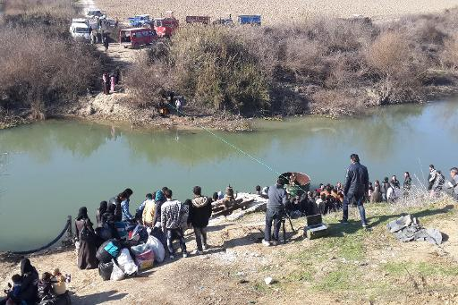 Displaced Syrians wait to cross the Orontes river into Turkey on February 5, 2014 at the Syrian-Turkish border in the Idlib province  (Shahba Press/AFP/File)