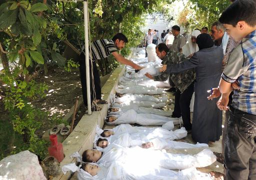 A man takes the body of a child wrapped in shrouds from a line of victims of the alleged toxic gas attack in the Ghouta district of Damascus in August  (SHAAM NEWS NETWORK/AFP, Daya al-Deen)