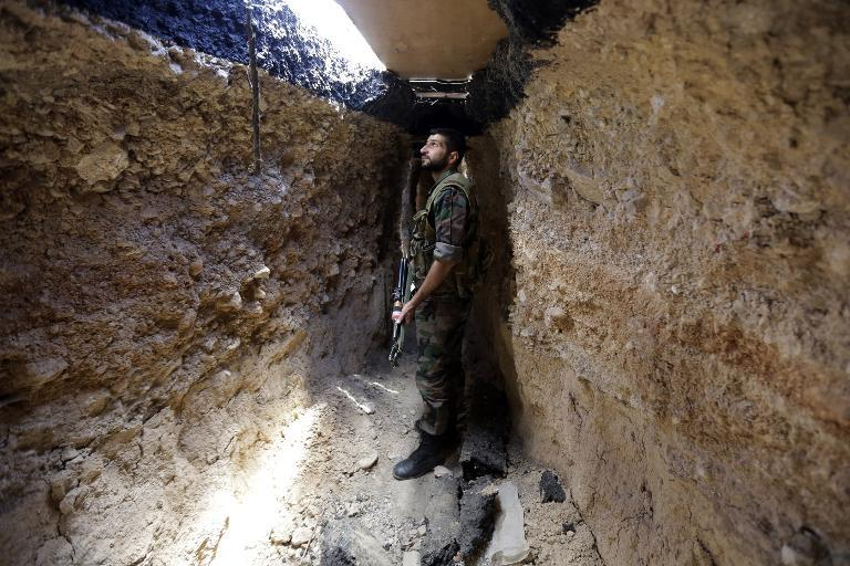 A Syrian army soldier makes his way in a tunnel reportedly previously used by rebel fighters in Jobar, on June 2, 2014  (AFP Photo/Joseph Eid)